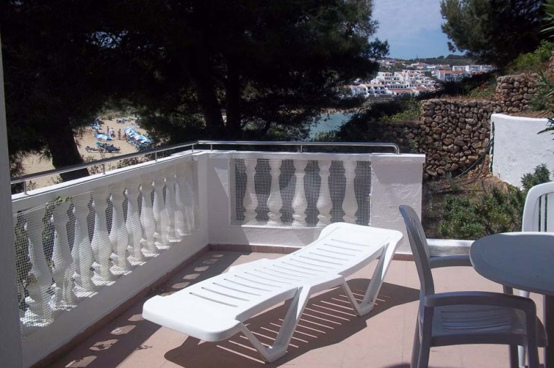 The terrace Jardín Playa 3 with sunbed for sunbathing in Menorca.
