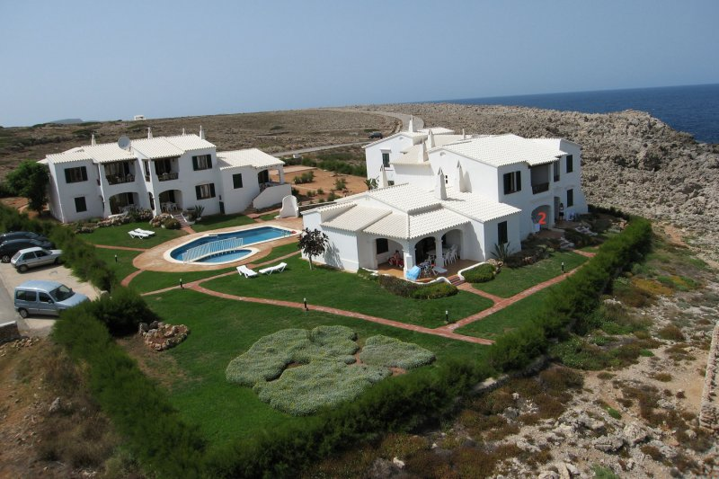View of the apartments Rocas Marinas from the air, with the coast of Menorca in the background.