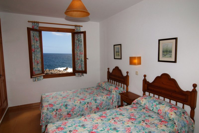 Room with window and two single beds of the Rocas Marinas 2R apartment.