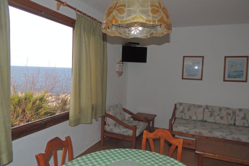 Living room with window to the sea and the nature of Menorca.