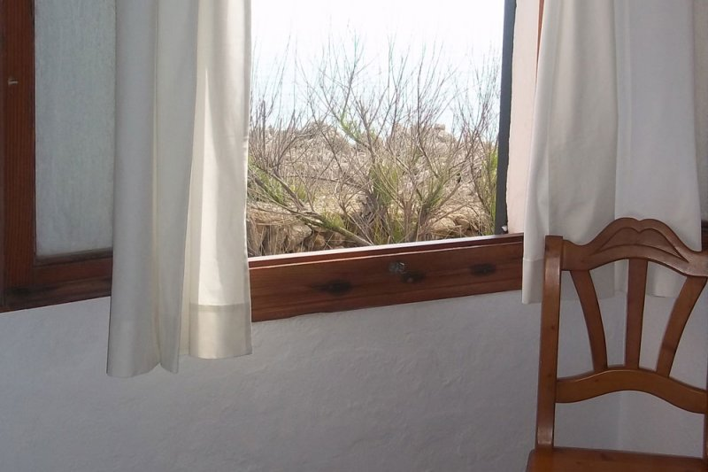Window of the master bedroom with views of the coast of Menorca.