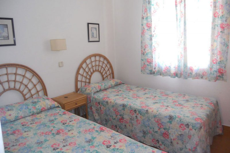 Bright bedroom with two single beds and window of the apartment Rocas Marinas 4R.