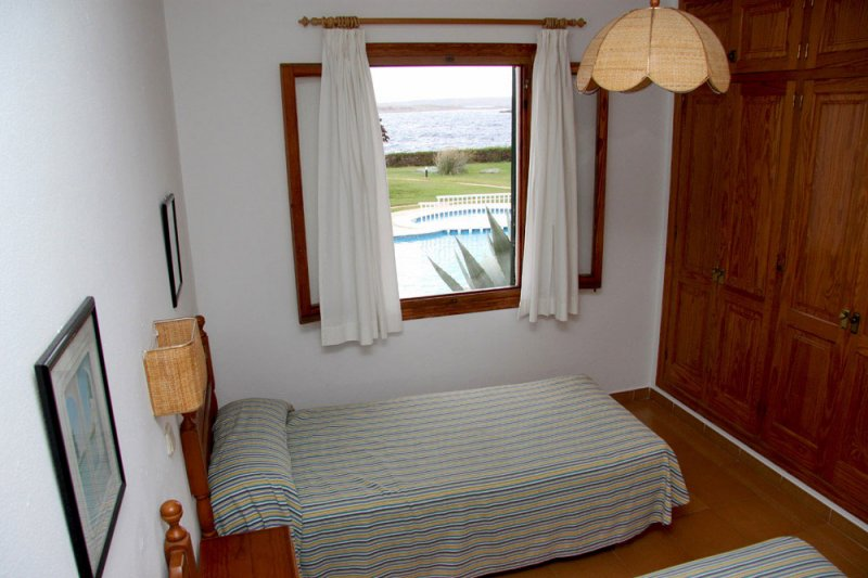 Bedroom with single beds and window overlooking the communal pool.