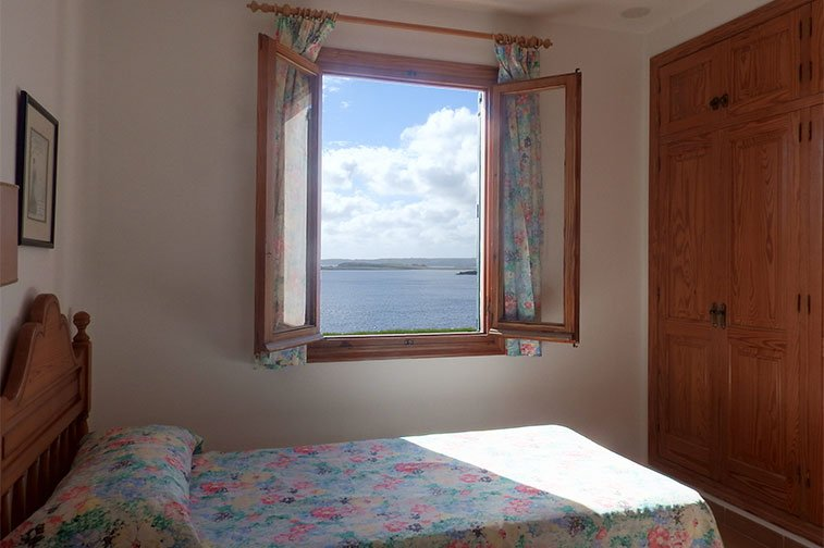 Window of the bedroom with single beds facing the coast of Menorca.