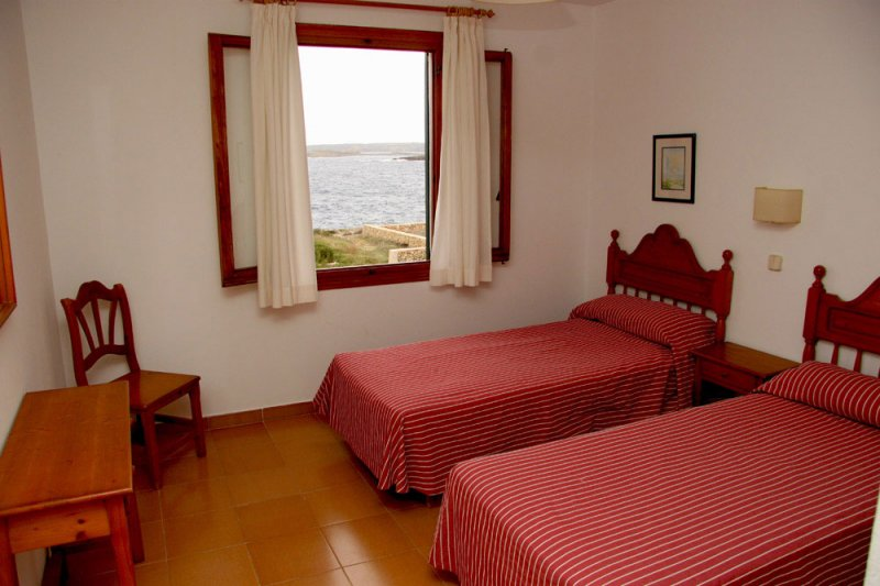 Well-lit room with single beds from the Rocas Marinas 8R apartment.