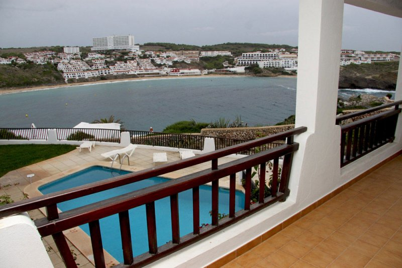 View to the pool of the Arco Iris apartments and the beach of s'Arenal d'en Castell, in Menorca.