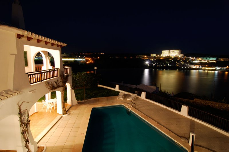 Night view of the Arco Iris apartments in Menorca and s'Arenal d'en Castell in the background.