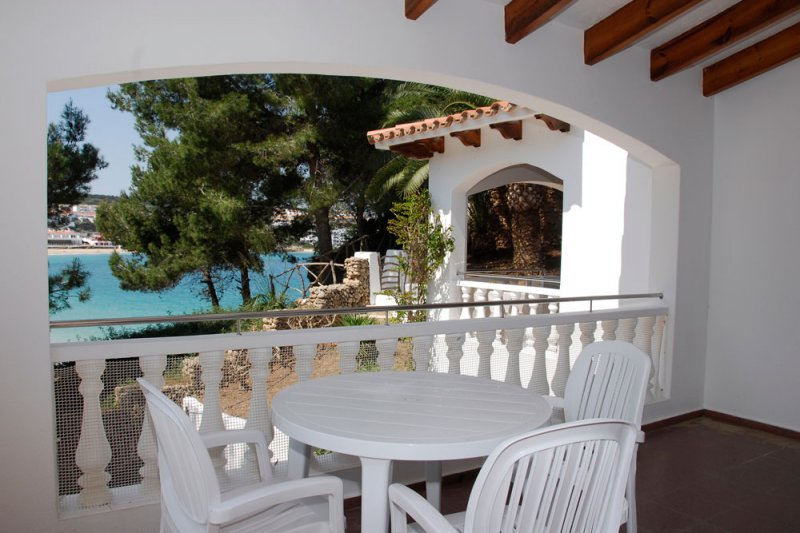 View of the covered terrace of the Jardín Playa 1 apartments, towards a beach in Menorca.