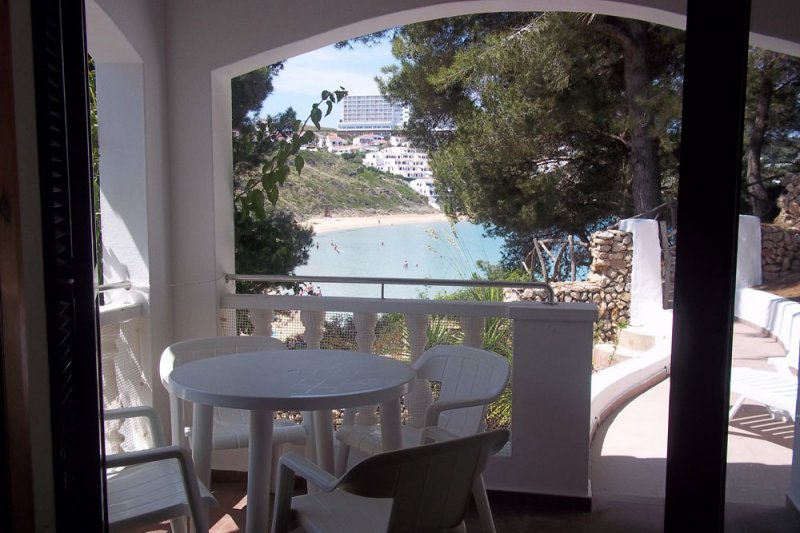 Covered terrace of the Jardín Playa 2 apartment with views of s'Arenal d'en Castell between the tree