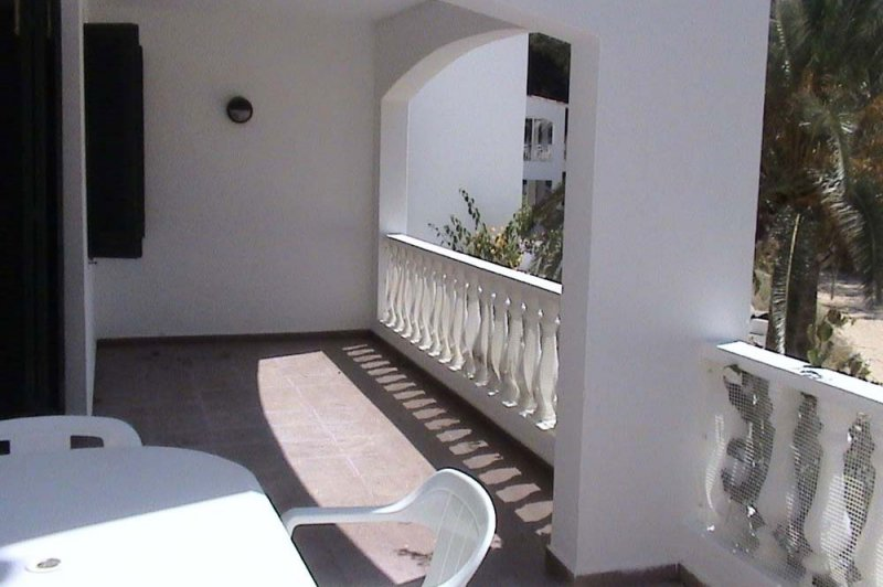 Covered terrace and balcony of the Jardín Playa 3 with access to the living room of the apartment.