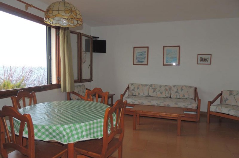 Spacious dining room of the Rocas Marinas apartment with touches of vintage decoration.