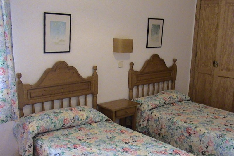 Bedroom of the Rocas Marinas 3 apartment, with double beds and traditional decoration.