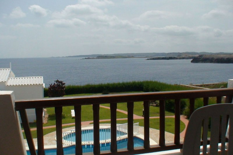 View from the terrace of the 8A Rocas Marinas apartment, to the pool and the coast of Menorca.