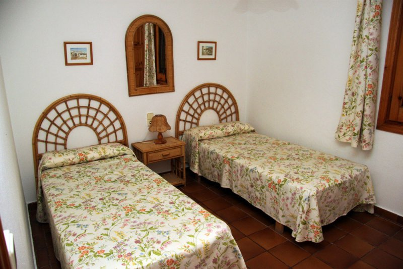 Bedroom with two separate single beds and traditional decoration of the Arco Iris 2 apartment