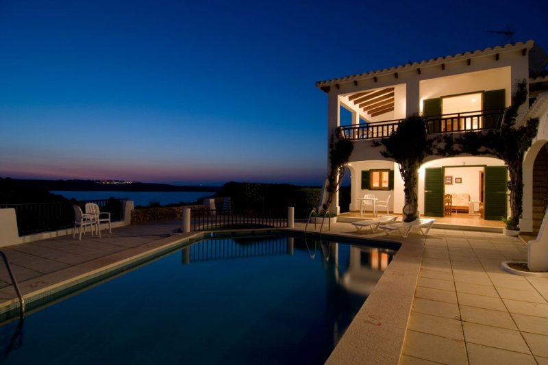 Night lighting of the Arco Iris apartments with a spectacular background of the coast of Menorca.