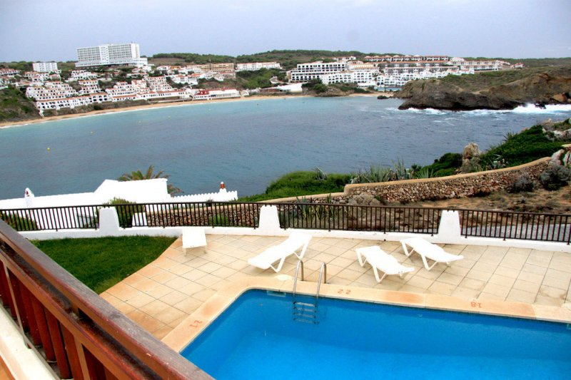 Views towards the pool of the Arco Iris apartments and the beach of s'Arenal d'en Castell.