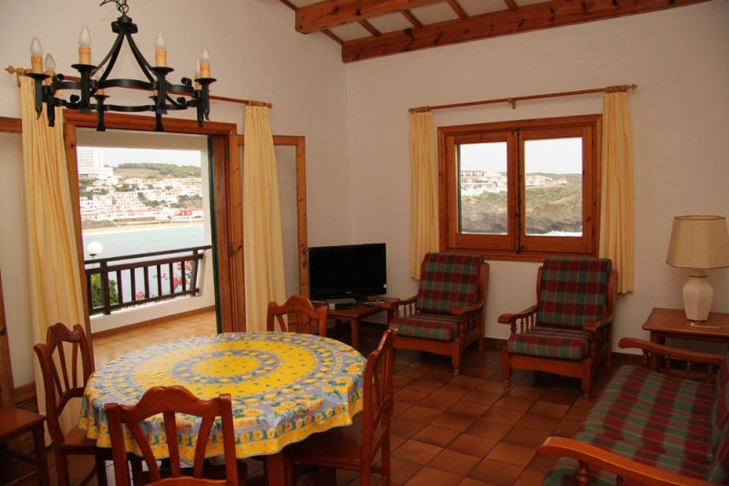 Spacious living room with access to the covered terrace of the Arco Iris 4 apartment.
