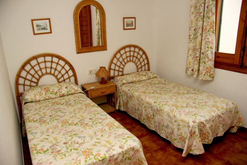 Room with two single beds of the Arco Iris 5 apartment with vintage touches.