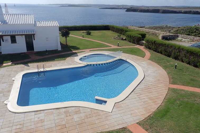 Top view of the community pool of the Rocas Marinas apartments and the coast of Menorca.